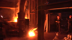Stock Video Footage of Loading of Iron Ore Into Blast Furnace Two Workers with Shovels are Loading the