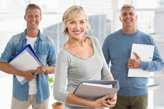 Smiling business colleagues holding workbooks - stock photo
