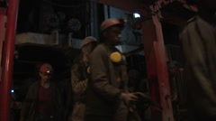 Crowd of Dirty Miners Are Walking in Uniform, Safety Helmets, Lamps on a Stock Footage