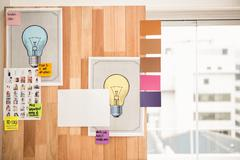 Illustrations and sticky notes on wooden wall - stock photo