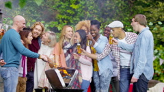 4K Happy group of friends at outdoor bbq raise their glasses for a toast Stock Footage