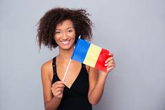 Afro american woman holding Romanian flag - stock photo
