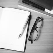 Stock Photo of open notebook with stack of book black and white color tone style