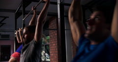 Three people doing chin up exercises on a pull up bar in a gym Stock Footage