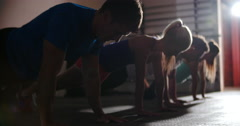 Four people doing push ups in gym Stock Footage