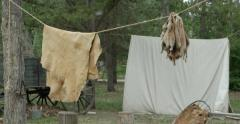 Animal pelts hang on rope in wild west camp. Stock Footage