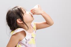 Sick Asian girl spray nasal medicine in nose. - stock photo