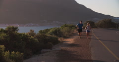 Couple running towards camera on a coastal road Stock Footage