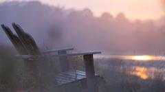 ADIRONDACK CHAIRS AT A LAKE AT SUNSET SLO--MO Stock Footage