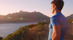 Man recovering after jogging admiring view on coastal road Stock Footage