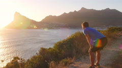 Young man taking a break from running on coastal road Stock Footage