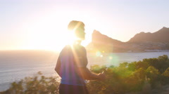 Man and woman admiring a coastal view after jogging Stock Footage