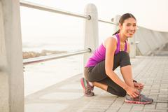 Stock Photo of Smiling fit woman tying shoelace at promenade