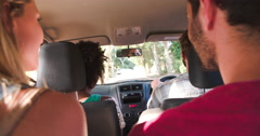 Friends talking in a car as they drive, view from back seat Stock Footage