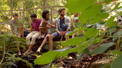 Friends sitting on bridge in forest Stock Footage