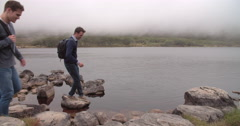 Four friends on a walk taking a break by the edge of a lake Stock Footage