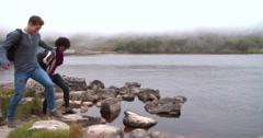 Couple on a walk taking a break by the edge of a lake Stock Footage