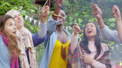 Joyful mixed ethnicity female friends holding sparklers at outdoor party - stock footage