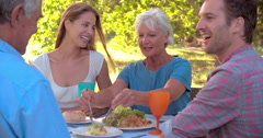 Multi-generation family eating together outdoors - stock footage