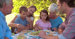 Four friends eating at a table together outdoors Stock Footage