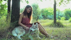 Stock Video Footage of young woman reads a book with a husky dog as a companion slow motion