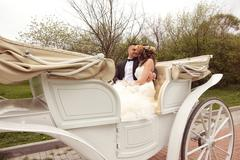 Bride and groom in a white carriage Stock Photos