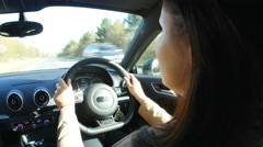Young woman driving in a car in a rural setting, head shot Stock Footage
