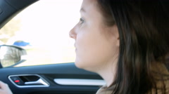 Young woman driving in a car, reflection in rear-view mirror Stock Footage