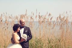 Bride and groom surrounded by rush - stock photo