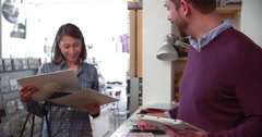 Close-up of hands sorting through records at a record shop Stock Footage