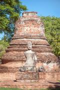 Damaged Buddha statue and ruined chedi at Wat Phra Si Sanphet, Ayutthaya, Tha Stock Photos