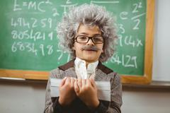 Little Einstein holding books in front of chalkboard Stock Photos