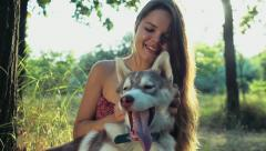 Teenage girl caresses a husky dog in forest slow motion Stock Footage