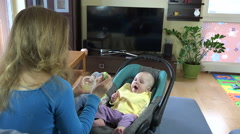 Sleepy baby girl eat vegetable pap with mother in room. 4K Stock Footage