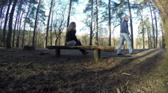 Couple sit on bench and man walk away. 4K Stock Footage