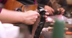 Close Up Of Shoemaker Applying Rubber Solution Glue To Shoe Stock Footage