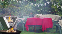 4K Outdoor summer party scene with flaming bbq, party banners and string lights Stock Footage