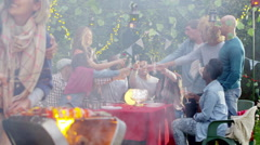 Happy couple share a kiss at bbq while friends socialize in the background.  Stock Footage