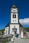 Tourists walk in front of the church in Roros, Norway. Stock Photos