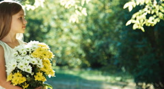 Girl in wite dress standing in the park and holding bouquet of white and yellow - stock footage