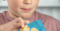 Teenage boy eating unhealthy snacks - stock footage