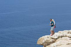 Two people watching the sea by a rocky precipice Stock Photos