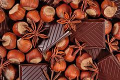 Chocolate, star anise and hazelnuts Stock Photos