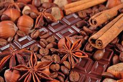 Coffee, chocolate, star anise, hazelnuts and cinnamon sticks close up - stock photo