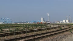 Freight train approaching in bend, ROTTERDAM seaport in bacground Stock Footage