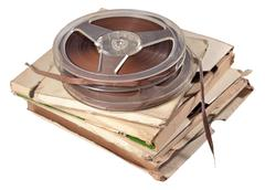 Old vintage bobbins with magnetic tapes on a white Stock Photos