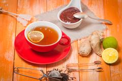 Cup of  tea with ginger,   raspberry jam and lemon - stock photo