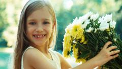 Portrait girl sniffing flowers. Child is in wite dress standing in the park - stock footage