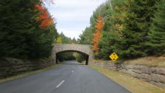 Driving under stone bridge on Acadia All American Road Stock Footage