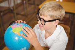 Stock Photo of Pupil looking at a globe of earth